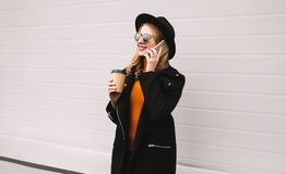 Elegant young woman calling on smartphone on city street. Wearing jacket coat, round hat, gray wall background stock photos
