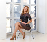 Elegant young woman in dress and high heel shoes. Sitting in modern chair Stock Image