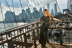Elegant young woman dressed in fashionable jumpsuit standing on the Brooklyn Bridge. Stock Photography