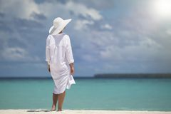 Elegant young woman in a hat standing on beach Royalty Free Stock Images