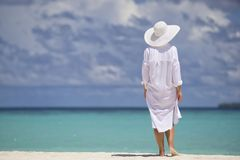 Elegant young woman in a hat standing on beach Stock Photo