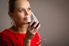 Elegant young woman having a glass of red wine Royalty Free Stock Photos