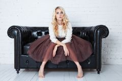 Elegant young woman in lush skirt sits on the couch. Concept fatigue Royalty Free Stock Photo