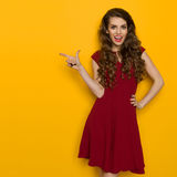 Elegant Young Woman Is Pointing And Talking Royalty Free Stock Photography