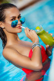 Elegant young woman in the pool with a cocktail. Royalty Free Stock Image
