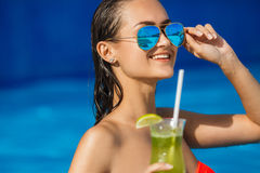 Elegant young woman in the pool with a cocktail. Royalty Free Stock Images