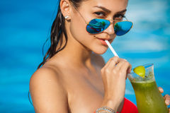 Elegant young woman in the pool with a cocktail. Stock Image