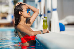 Elegant young woman in the pool with a cocktail. Stock Photos