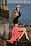 Elegant young woman posing pretty at the pier with water on the background. Stock Image