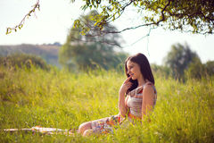 Elegant young woman posing in sunny park Stock Photos