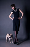Elegant young woman with a pug dog in studio. Beautiful fashion brunette girl in a dress together with a pug dog in a bow tie in a studio environment Royalty Free Stock Photos