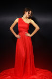 Elegant young woman in red dress. On black background Royalty Free Stock Image