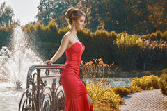 Elegant young woman in red dress standing in front of fountain. Elegant young woman in red dress standing in front of fountain in the park Royalty Free Stock Photos