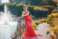 Elegant young woman in red dress standing in front of fountain. Stock Image