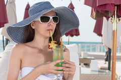 Elegant young woman sipping an ice cold cocktail Royalty Free Stock Images