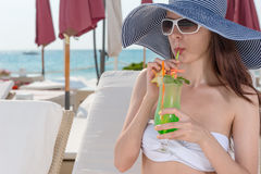 Elegant young woman sipping a tropical cocktail Stock Photography