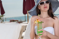 Elegant young woman sipping a tropical cocktail Royalty Free Stock Photos