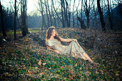 Elegant young woman sit on ground in forest Royalty Free Stock Image