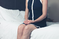 Elegant young woman sitting on bed in hotel room Royalty Free Stock Photography