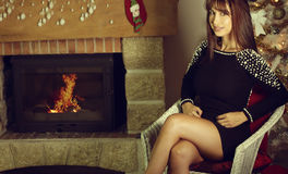 Elegant young woman sitting on a chair next to a fireplace Stock Image