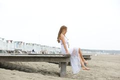 Elegant young woman sitting by the seaside Royalty Free Stock Photos