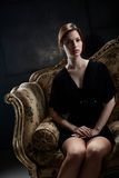 Elegant young woman sitting on sofa Stock Image