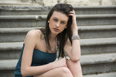 Elegant young woman sitting on stone steps outdoors Royalty Free Stock Images