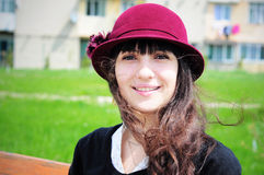 Elegant young woman smiling outdoors. Portrait of an elegant young woman, wearing hat, smiling in the park Stock Images