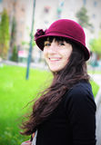 Elegant young woman smiling outdoors. Portrait of an elegant young woman, wearing hat, smiling in the park Royalty Free Stock Photos