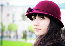 Elegant young woman smiling outdoors. Portrait of an elegant young woman, wearing hat, smiling in the park Royalty Free Stock Images