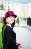 Elegant young woman smiling outdoors. Portrait of an elegant young woman, wearing hat, smiling in the park Royalty Free Stock Photography