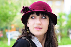 Elegant young woman smiling outdoors. Portrait of an elegant young woman, wearing hat, smiling in the park Stock Photo
