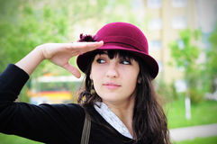Elegant young woman smiling outdoors. Portrait of an elegant young woman, wearing hat, smiling in the park Stock Photography