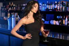 Elegant young lady at the bar. Elegant young woman standing at the bar, celebrating with drink, looking at camera Royalty Free Stock Photos