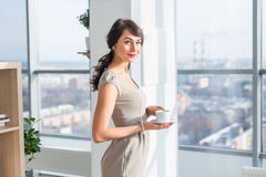 Elegant young woman standing in a spacious light studio, drinking cup of coffee, smiling, dreaming near large window Royalty Free Stock Photography