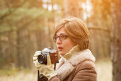 Elegant young woman taking photo in the forest Stock Image