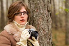 Elegant young woman taking photo in the forest in autumn Stock Photos