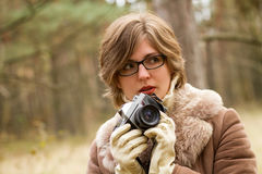 Elegant young woman taking photo in the forest Stock Photos