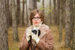 Elegant young woman taking photo in the forest Royalty Free Stock Photography