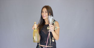 Elegant young woman toasting the New Year. Elegant young woman in a black cocktail outfit toasting the New Year with a bottle and flute of champagne raising her Stock Photography