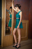 Elegant young woman in turquoise short dress looking into a large mirror, side view. Beautiful slim girl with creative hairstyle Stock Photos