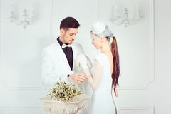 Bride adjusting boutonniere on jacket of groom royalty free stock photography