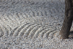 Elegant Zen garden with raked sand. Peaceful Zen garden with raked sand and single tree trunk. Gravel's classical pattern represents water flow and movement Stock Photos