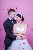 Eleganta brölloppar som omfamnar, medan stå mot rosa bakgrund Royaltyfri Bild