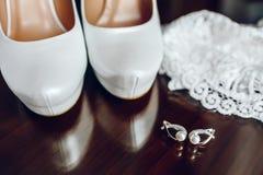 Eleganta brud- skor och silverörhängen med pärlan Royaltyfri Bild