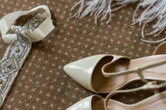 Eleganta brud- skor på en brun matta Arkivbilder
