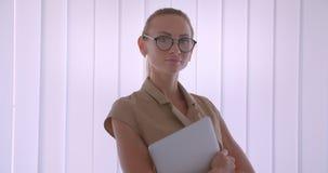 Eleganta caucasian klockor för affärskvinnainnehavbärbar dator in i kamera fast beslutsamt och stå i stillhet nära fönstret stock video