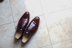 Eleganta eleganta skor för brudgum på golvet Royaltyfri Fotografi