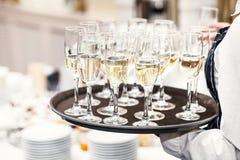 Eleganta exponeringsglas med Champagne Standing i rad på att tjäna som Tabl arkivfoto