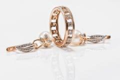 Eleganta guld- örhängen med pärlor och en tjock cirkel med litet D Arkivfoto